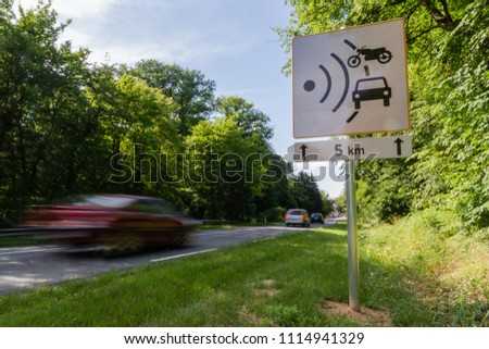 Speed limit speed camera sign with cars driving too fast #1114941329