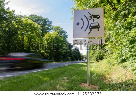 Speed limit speed camera sign with cars driving too fast #1125332573