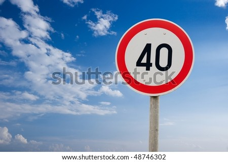 Speed limit traffic sign against bright sky