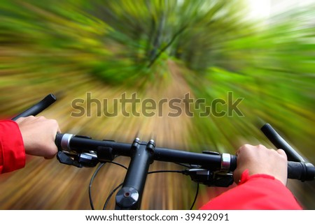 Speed on Mountainbike. Biking in the forest motion blurred for speed effect