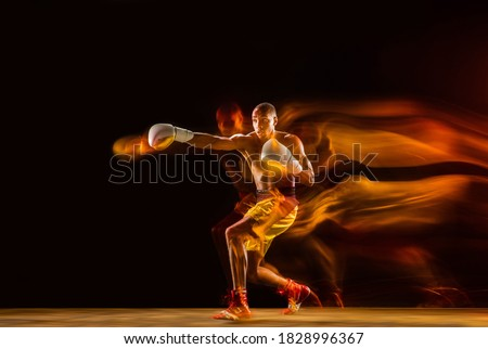 Photo of  Speed. Professional boxer training isolated on black studio background in mixed light. Man in gloves practicing in kicking and punching. Healthy lifestyle, sport, workout, motion and action concept.