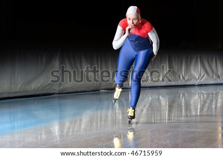 Speed skater emerging on the straight stretch of an indoor ice rink during a long distance skating race