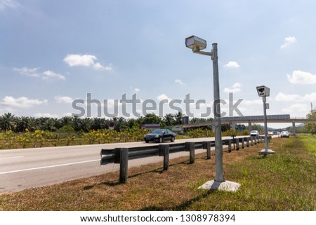 Speed trap surveillance camera along highway to control speeding to reduce speeding related accident #1308978394