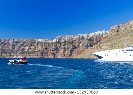 Speedboat at high volcanic cliff of Santorini island in Greece