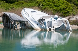 Speedboat beached and partially sunk at it's mooring