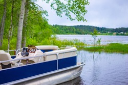 Speedboat on the background of a picturesque lake. Water recreation. Boating. Boat rental. Boat station. Water transport for walking.