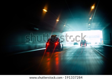 Speeding car inside a highway tunnel exiting to white calm light