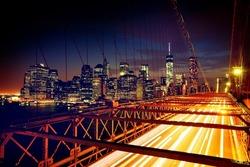 Speeding cars on Brooklyn Bridge, Downtown Manhattan, New York. Night scene. Light trails. City lights. Urban living and transportation concept