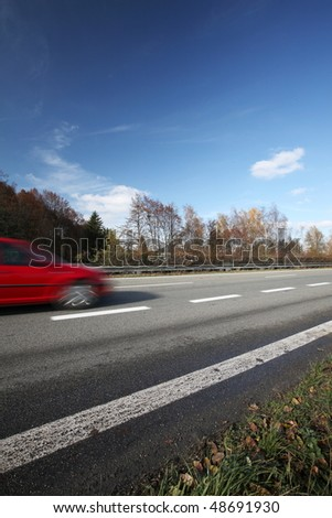 Speeding concept - Cars moving fast on a highway on a lovely autumn/fall day (the cars are motion blurred to convey movement) #48691930