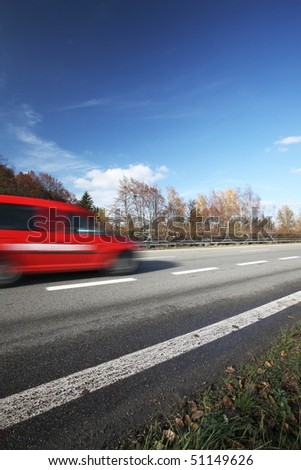Speeding concept - Cars moving fast on a highway on a lovely autumn/fall day (the cars are motion blurred to convey movement)