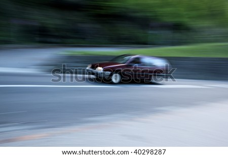 Speeding concept - motion blurred car going fast on a small road up the hill - stock photo