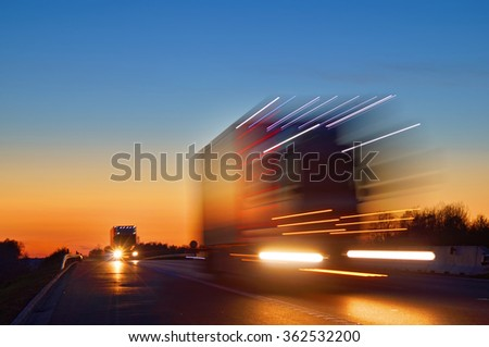 Speeding motion blur oncoming trucks with glowing lights on the highway after sunset. Shining the spotlight cars. Blue and orange bright sky at dusk.