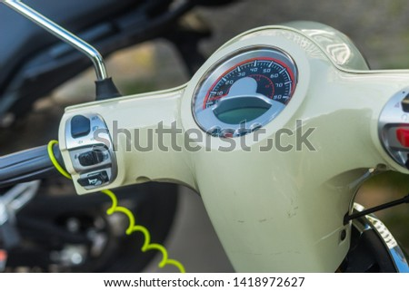 Speedometer of a light olive green vintage scooter with a bike in the background #1418972627