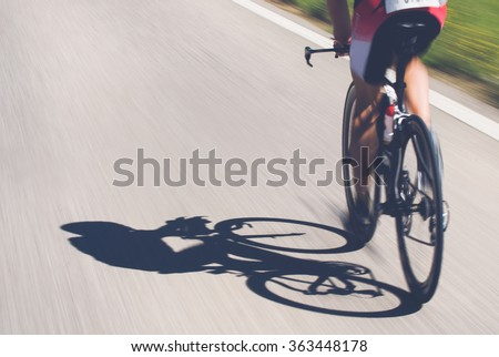 Speedy shadow - A cyclist at top speed on the triathlon race.