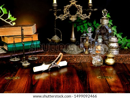 Spell books and bottles, dark candlestick with balance scale on a wooden table. Recipes of magic potions. Concept of alchemy. Imagination of the reader, inspiration for writing.