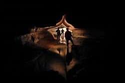 Spelunkers exploring a mystic cave river