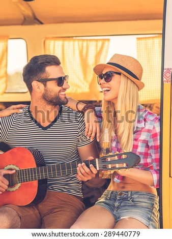 Spending carefree time together. Handsome young man sitting in minivan and playing guitar while his girlfriend bonding to him and smiling