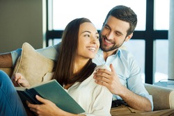 Spending great time together. Beautiful young loving couple bonding to each other and smiling while woman holding a book