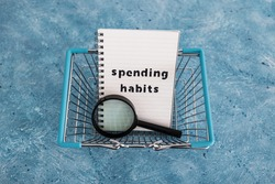 spending habits text on notepad with shopping basket and magnifying glass, money and consumer behaviour conceptual image