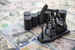 Spending or investment of a country's revenues from petroleum exports industry (Petrodollar). Oil pump jack and barrels on US dollar banknotes. Concept of crude oil production, petroleum industry.