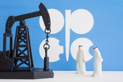 Spending or investment of a country's revenues from petroleum exports industry (Petrodollar). Oil pump jack and arab men with OPEC flag background. Concept of crude oil price down plummet, petroleum.