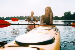 Spending quality time together. Beautiful young couple kayaking on lake together and smiling