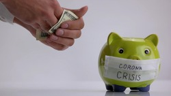 Spending savings for coronavirus crisis. Green piggy bank with facial mask on white backgrond.