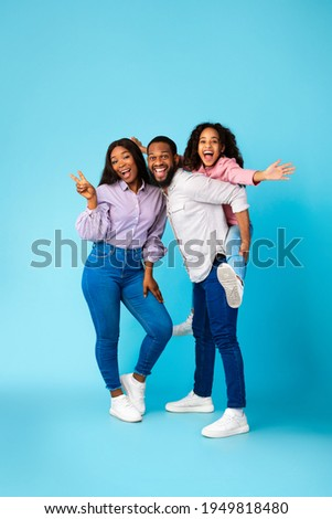 Spending Time With Family Is Fun. Full body length of excited African American man, woman and girl laughing and posing isolated over yellow studio wall. Cheerful father carrying his daughter on back