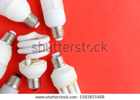 Spent incandescent halogen, cfi fluorescent, led, lumens light and energy saving bulbs tube, red background. Lamps containing mercury - extremely hazardous waste, very toxic to human health.Copy space