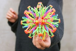 Sphere hoberman. A folding ball of rainbow color in the girl's hand. Educational toy for children.