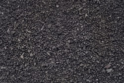 Spherical lumps of crushed ore concentrate close-up. Semi-finished product of metallurgical production of iron. Product of concentration of iron-bearing ores and subsequent pelletizing and roasting.