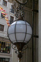 Spherical vintage lamp beside the wall, hanging iron grate patterned street lamp round shape with white glass, close-up ball-shaped lantern with metal cast elements, vertical photo.