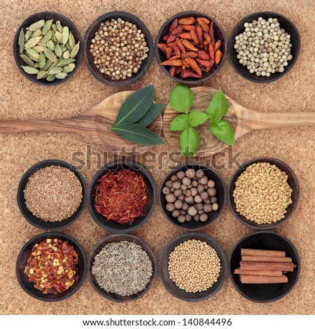 Spice, herb and food ingredient sampler in wooden spoons and bowls over cork background.