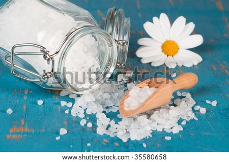 Spice jar with rock salt crystals spilling onto rustic table with wooden scoop