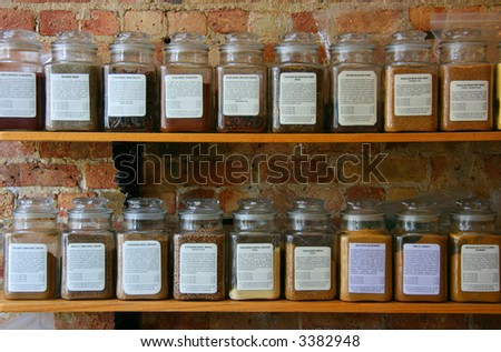 Spice jars on wooden shelf on a brick wall
