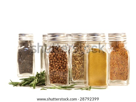 Spice jars with fresh rosemary leaves against white background