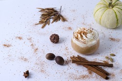 Spice pumpkin latte in a small Glass Cup with Cream and Cinnamon. Cozy warm Autumn drink concept with Pumpkin, cinnamon sticks, cardamom, star anise on white background with copy space.