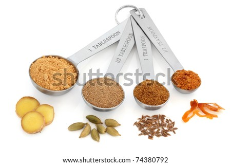Spice selection of ginger, cardamom, cumin and mace in ground form in stainless steel measuring spoons with corresponding whole spices over white background.  Left to right. Selective focus.