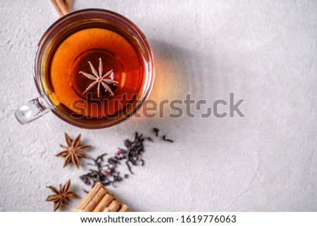 Spiced aromatic black tea. Hot warming beverage in a glass cup with anise and cinnamon on grey background