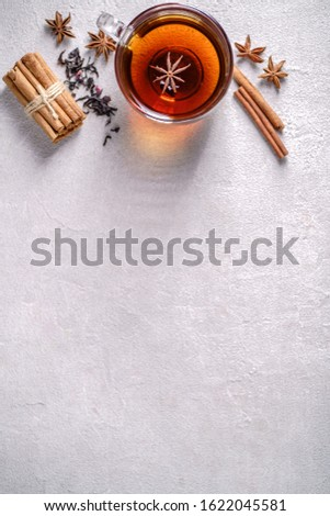 Spiced aromatic black tea. Hot warming beverage in a glass cup with anise and cinnamon on stone background
