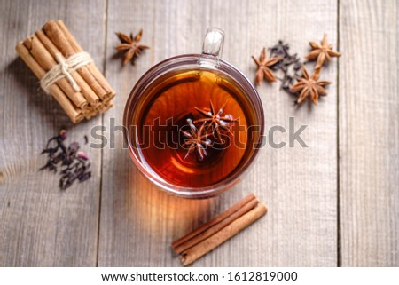 Spiced aromatic black tea. Hot warming beverage in a glass cup with anise and cinnamon on wooden background