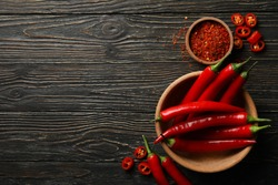 Spices and bowl with chilli pepper on wooden background