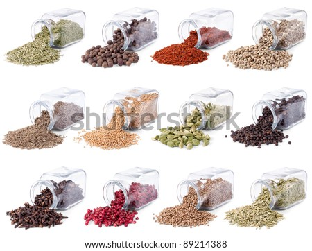 Spices and herbs are scattered on a white background from glass bottles