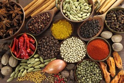 Spices and herbs in metal  bowls and wooden spoons. Food and cuisine ingredients.
