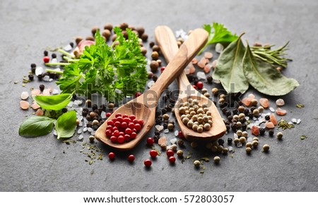 Spices and herbs on a black board - Shutterstock ID 572803057