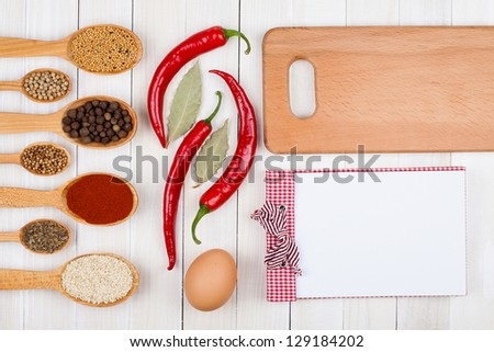 Spices, chili, egg, recipe book, wooden plank on white wood background