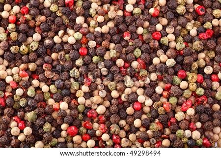 Spices closeup. The background of black, white, green and pink Peppercorns.