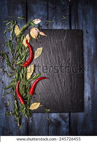 Spices food background with slate on blue wooden table, top view, place for text