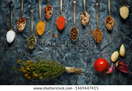 Spices in a spoon. Spices in a spoon, a tomato and a bunch of St. John's wort on a dark background. View from above.