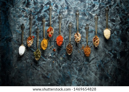 Spices in a spoon. Spices in a spoon on a dark background. View from above.